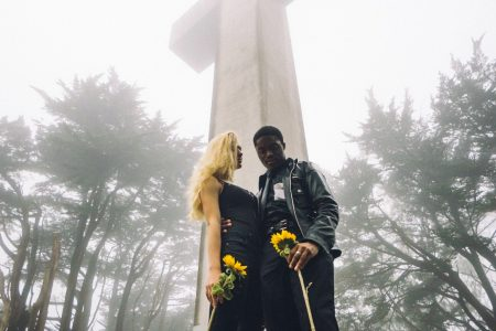 Couple standing in front of large cross